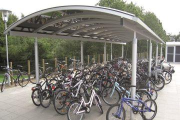 Åben cykeloverdækning med redskabsrum ved skole